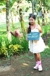 The junior maid of honor carrying HERE COMES THE BRIDE SIGN
